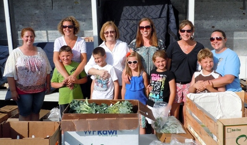 Nine-year-old Owen Ronning, center, raised money to bring a Mobile Food Pantry to his Hudsonville community last summer.