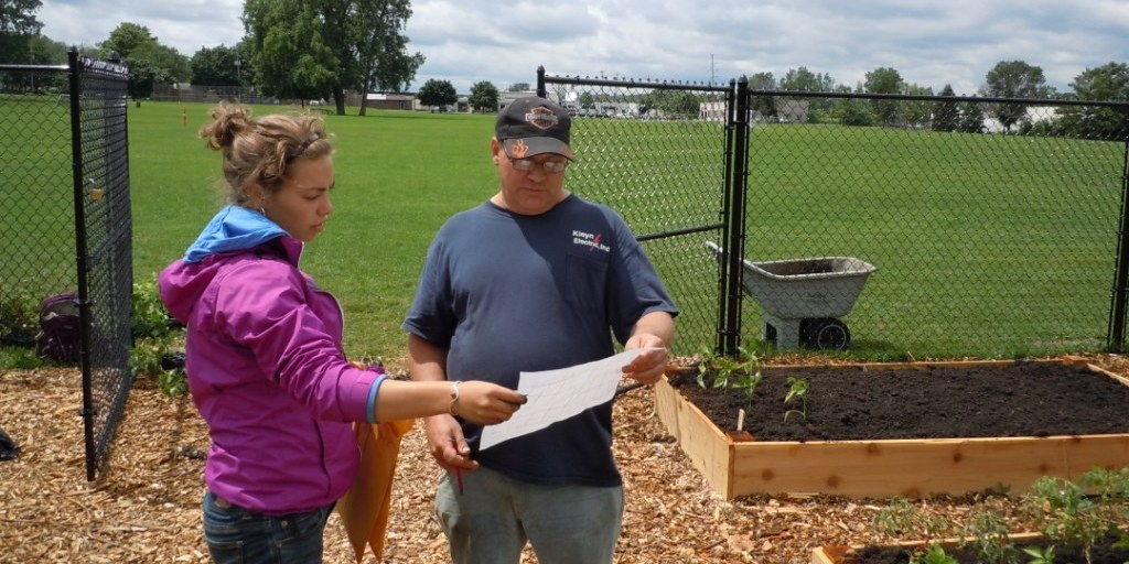 Miriam from Metro Health and Bob, a UCOM neighbor, review the plans for the agency's new community garden in Wyoming, Michigan.