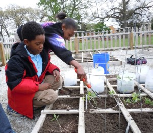 D'Mikol, left, and a classmate plant green beans at Congress Elementary School.