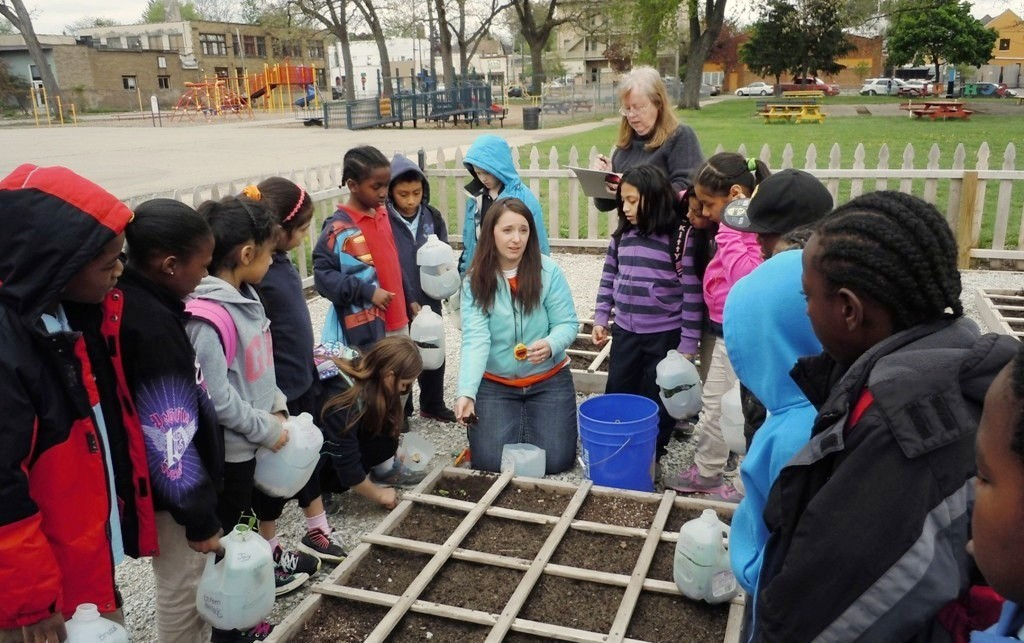Renee Howard shows her third graders how to plant vegetables at the Congress Elementary School garden.