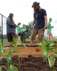 Volunteers plant peppers, tomatoes, and lettuce at UCOM's newest community garden.