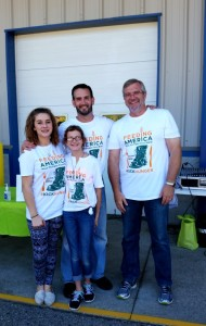 Food Bank CEO Ken Estelle, right, stands with operations manager Chad DeVries and Chad's daughters Taylor and Madelyn.