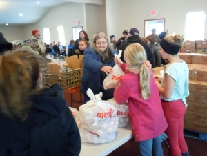 Students help Brandy's mother-in-law Pam with groceries at the American Legion's Mobile Pantry.