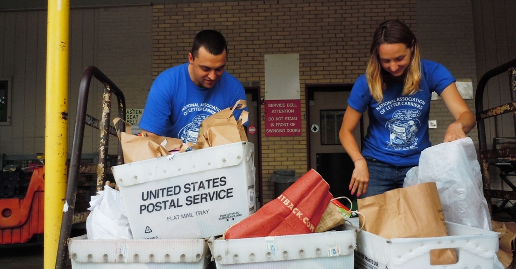 Food Bank staff members Ryan VanMaldegen and Katie Auwers unload donations during Stamp Out Hunger 2015.