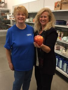 Judy, left, and Barb show off the enormous apples they picked for the pantry shelves.