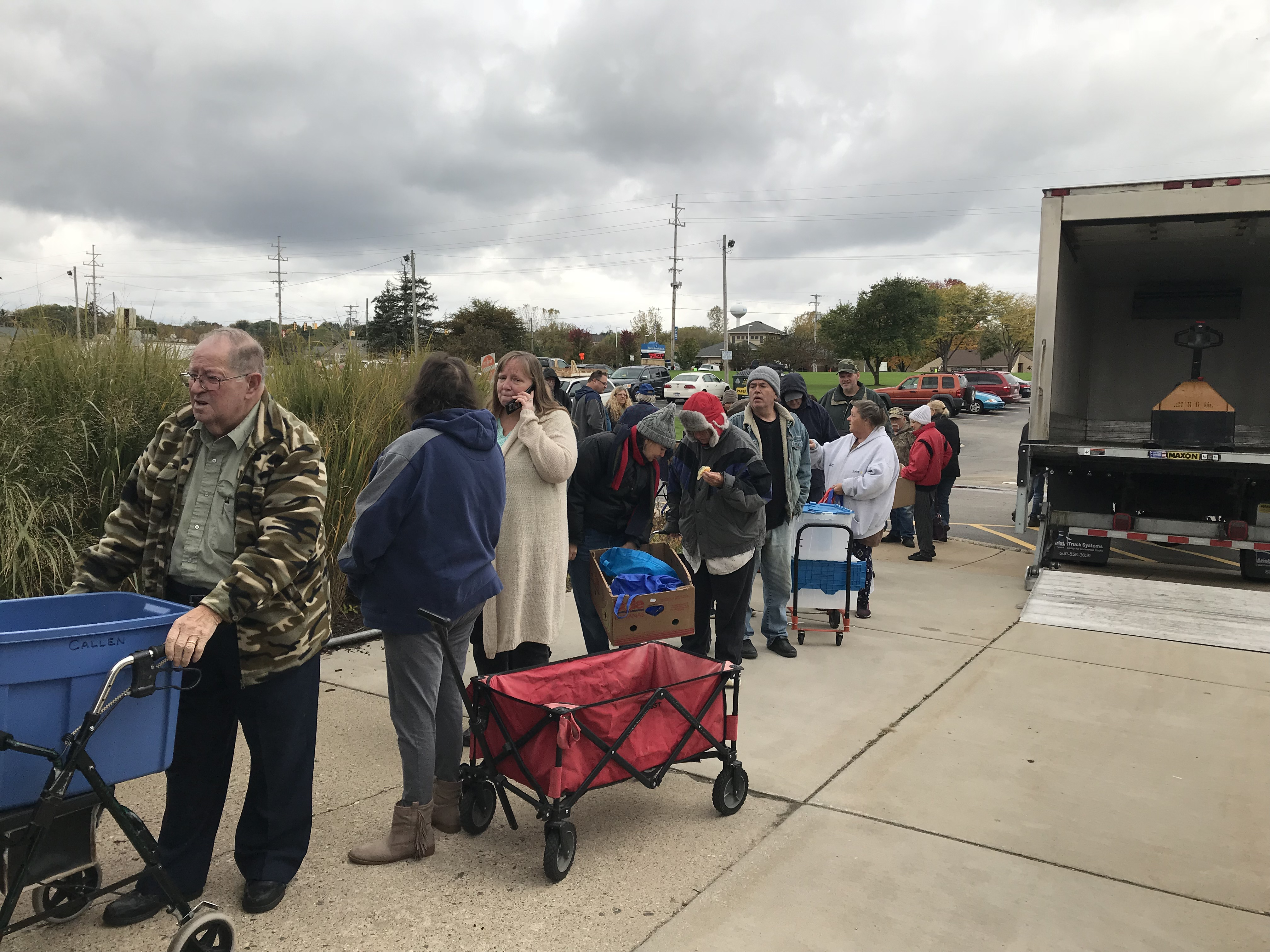 people lined up to recieve food from a mobile food pantry
