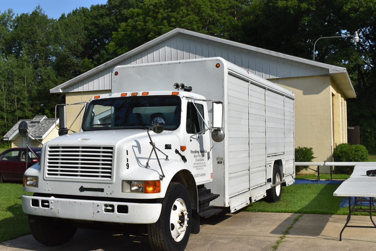 A large white Feeding America West Michigan truck waits for the food distribution.