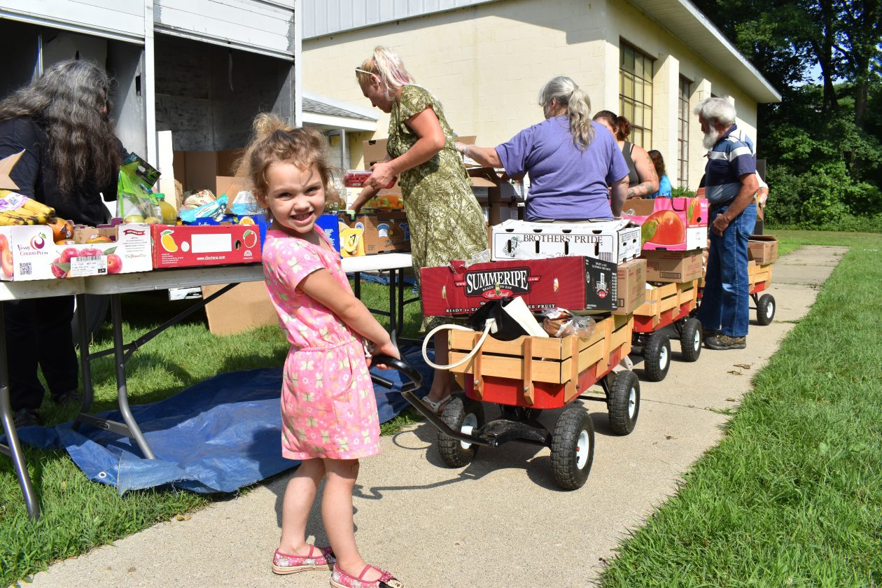 Navaeh pulls a wagon full of food through the distribution line, as her mom shops. She's smiling at the camera.