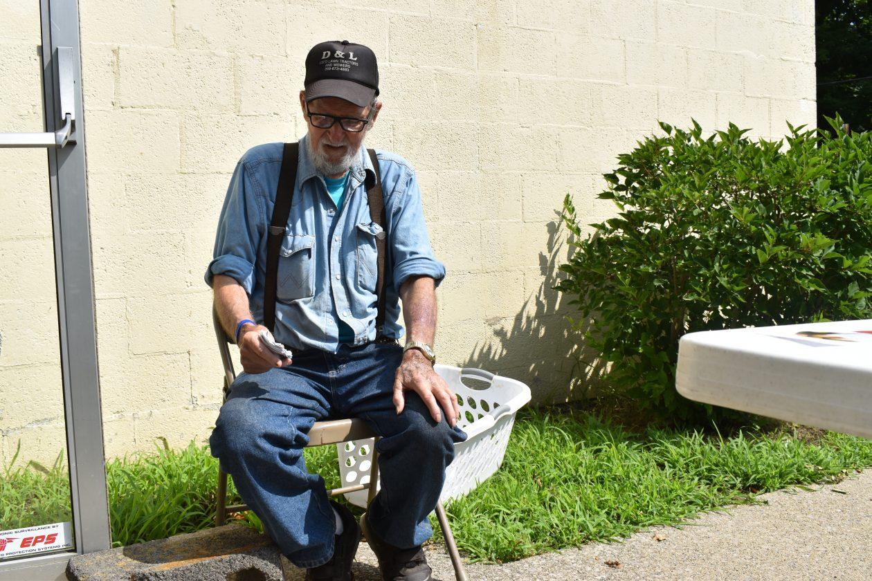 Older volunteer sits in a chair after volunteering.