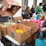 A girl reaches for food at a Mobile Food Pantry.