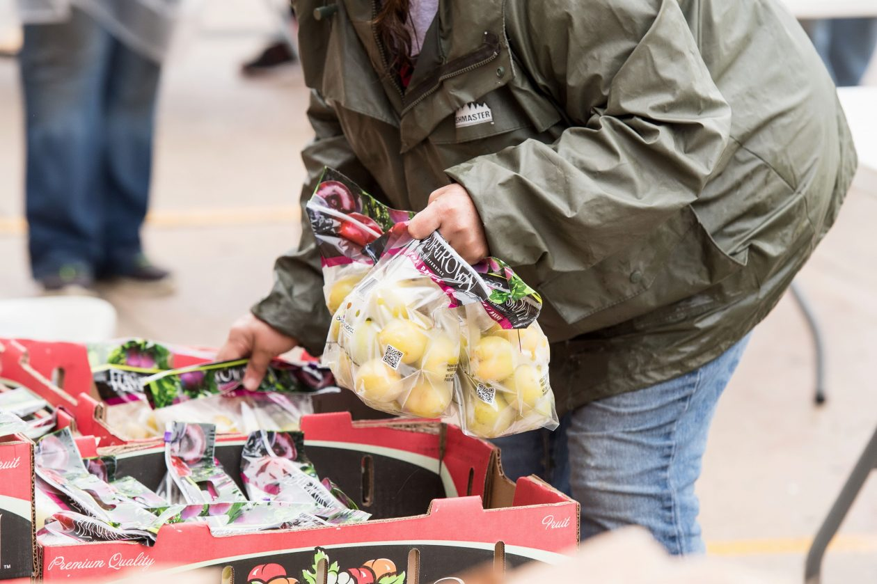 A client receives fruit from a Mobile Food Pantry.