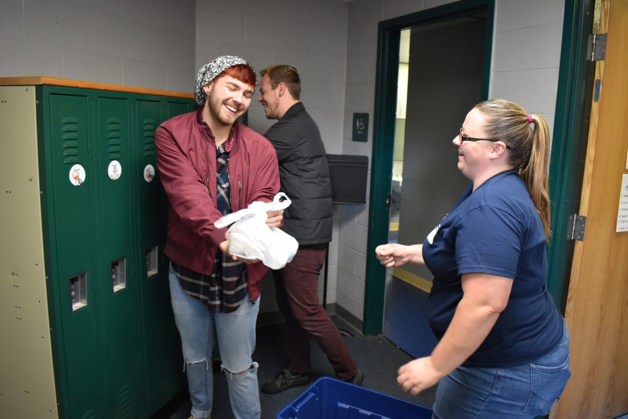 Volunteers place bags of food into lockers. One is smiling as another hands him a bag.