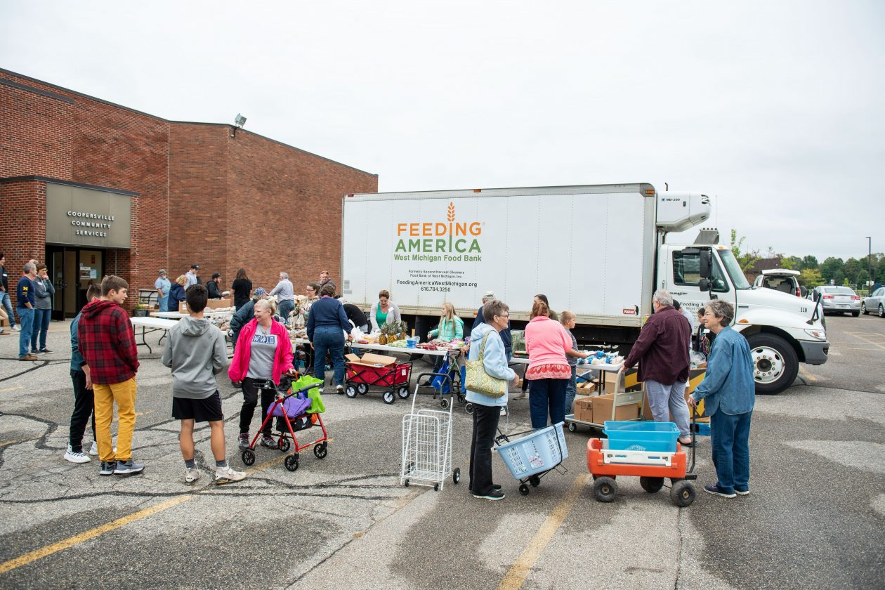 Neighbors line up at a Mobile Food Pantry with a truck in the background.