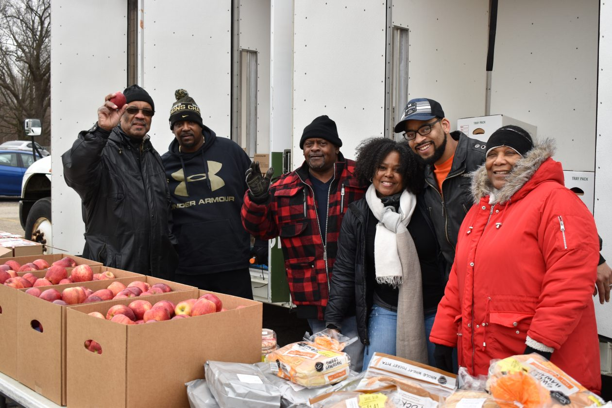 Group of volunteers poses with food and smiles at camera
