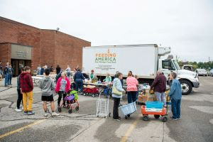 People wait in line to receive food at a Mobile Pantry.