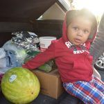 little boy sitting in car with with food