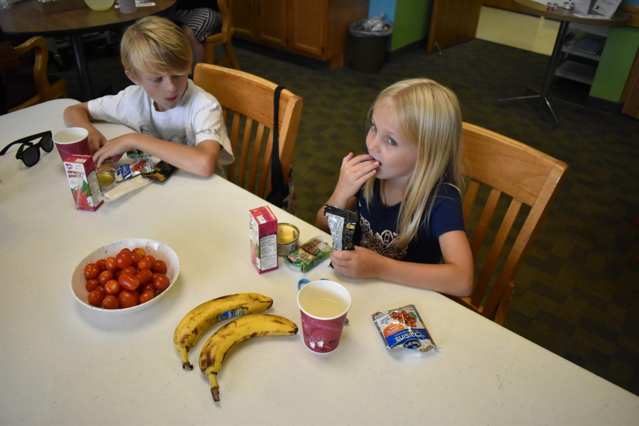 Children eat a meal at a meal site.