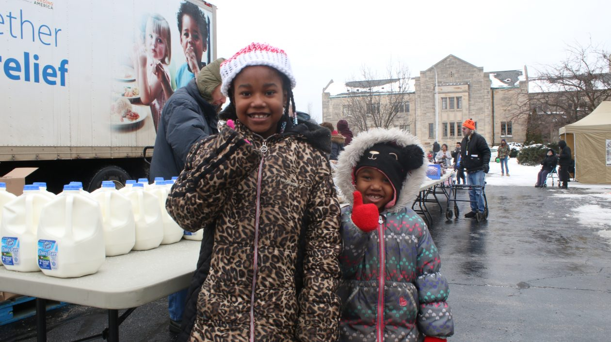 Two little girls smile at the camera while waiting at the Mobile Pantry