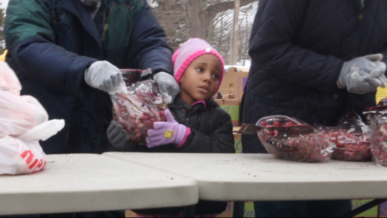 A little girl passes out grapes at the Mobile Pantry.