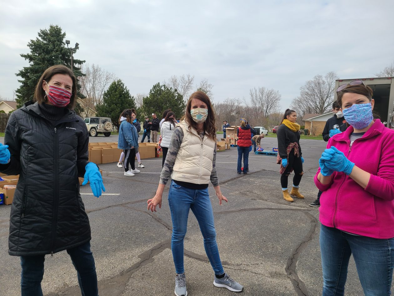 Three volunteers look at the camera wearing masks and gloves.