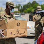 National guard member helps at a drive-thru food distribution.