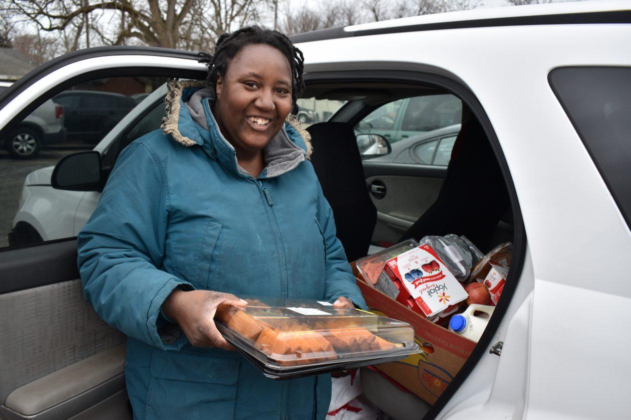 Monique puts food in her car.