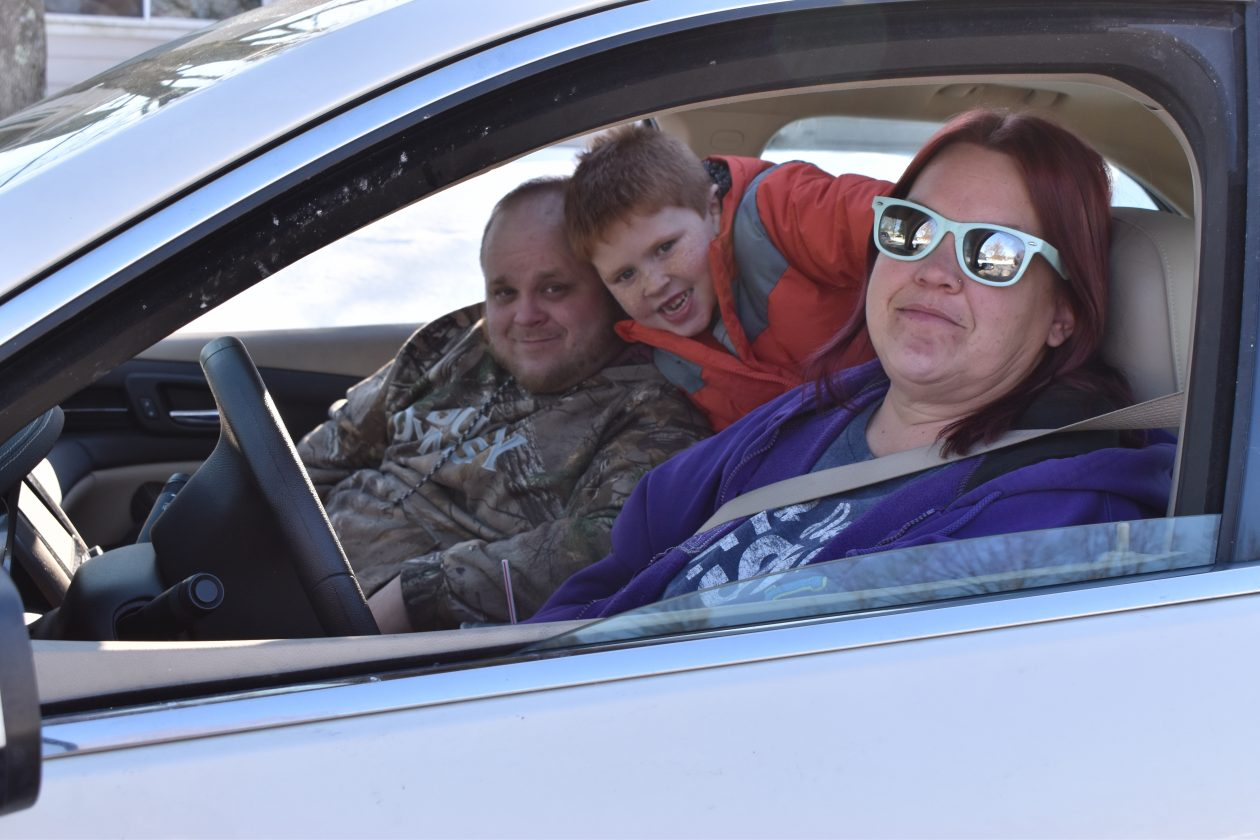 Julie, Chris and Cameron sit in their car while waiting at a Mobile Pantry.