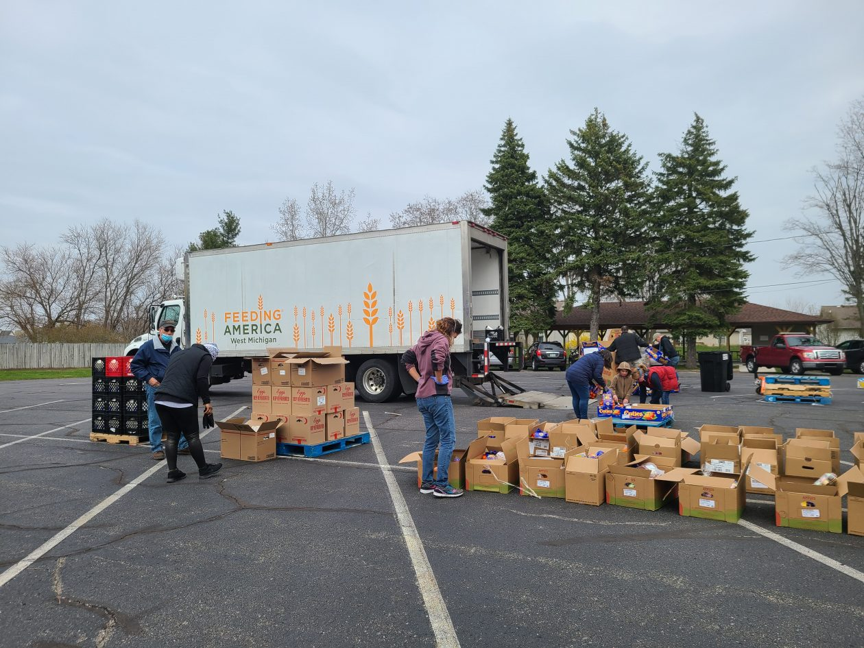 A bunch of boxes and volunteers surround a Mobile Pantry truck