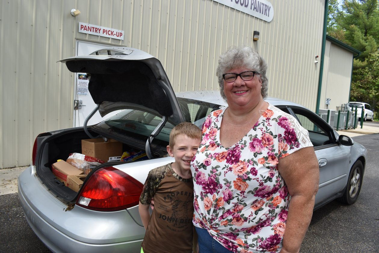 Theresa and her grandson stand in front of their car after receiving food.