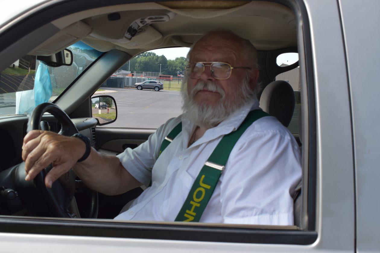 "Dan, a senior, sits in his car. He wears suspenders that say ""John Dear"" on them."
