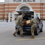 Kim and fellow National Guard member filling a trunk with food