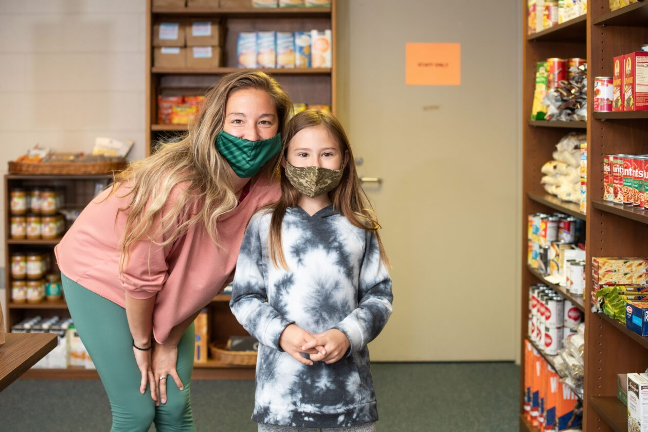 Mary Ann and Madison pose with food pantry shelves behind them