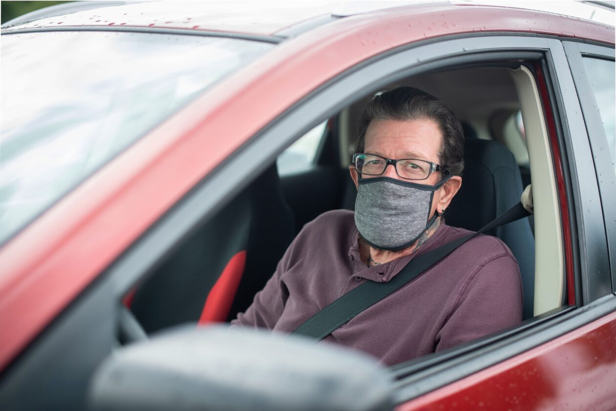 A middle aged man wearing a mask sits in his car