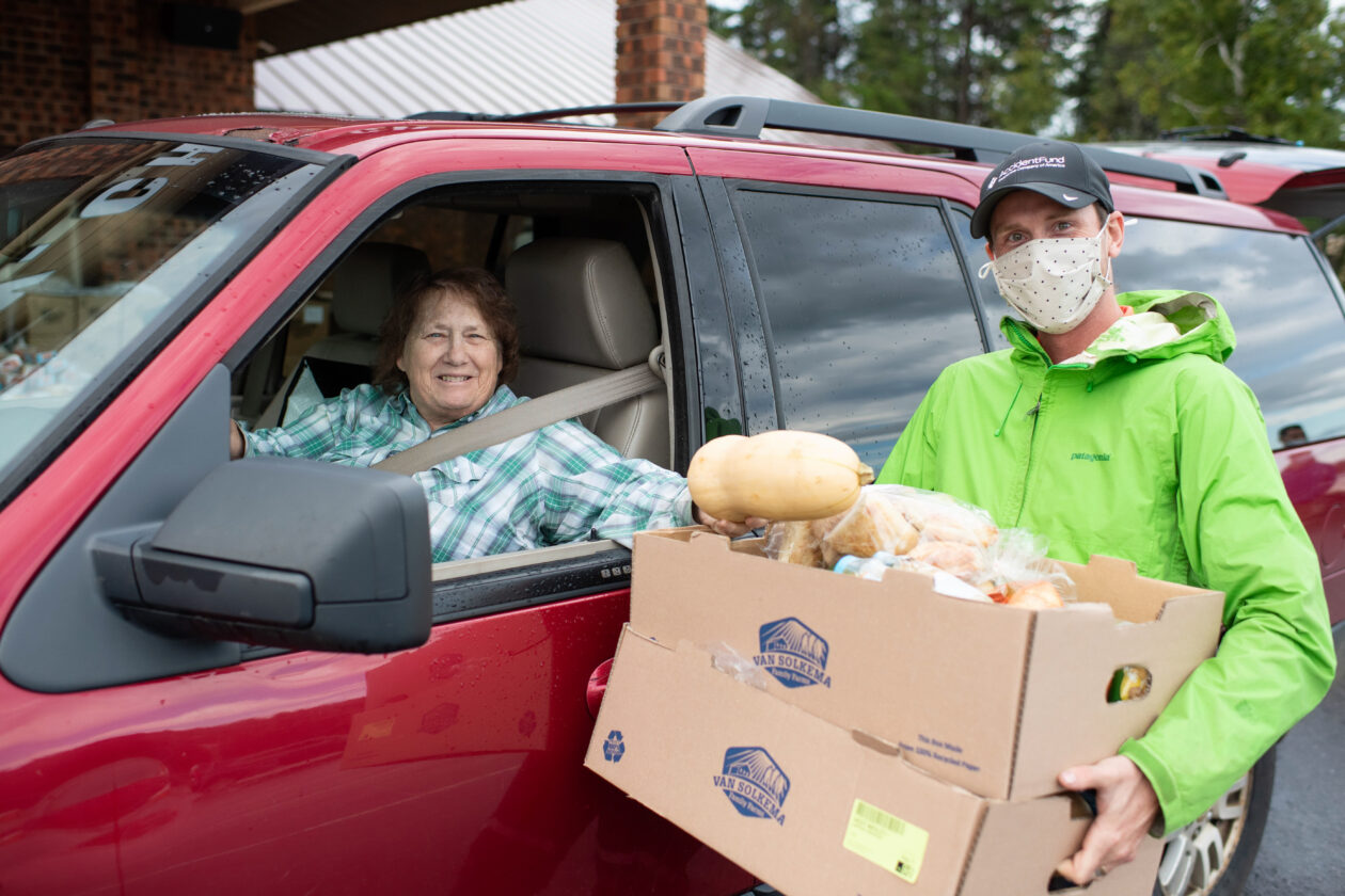 A volunteer carries a box of food while a client waits in a car.