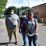 The three community coordinators stand in front of a Mobile Pantry