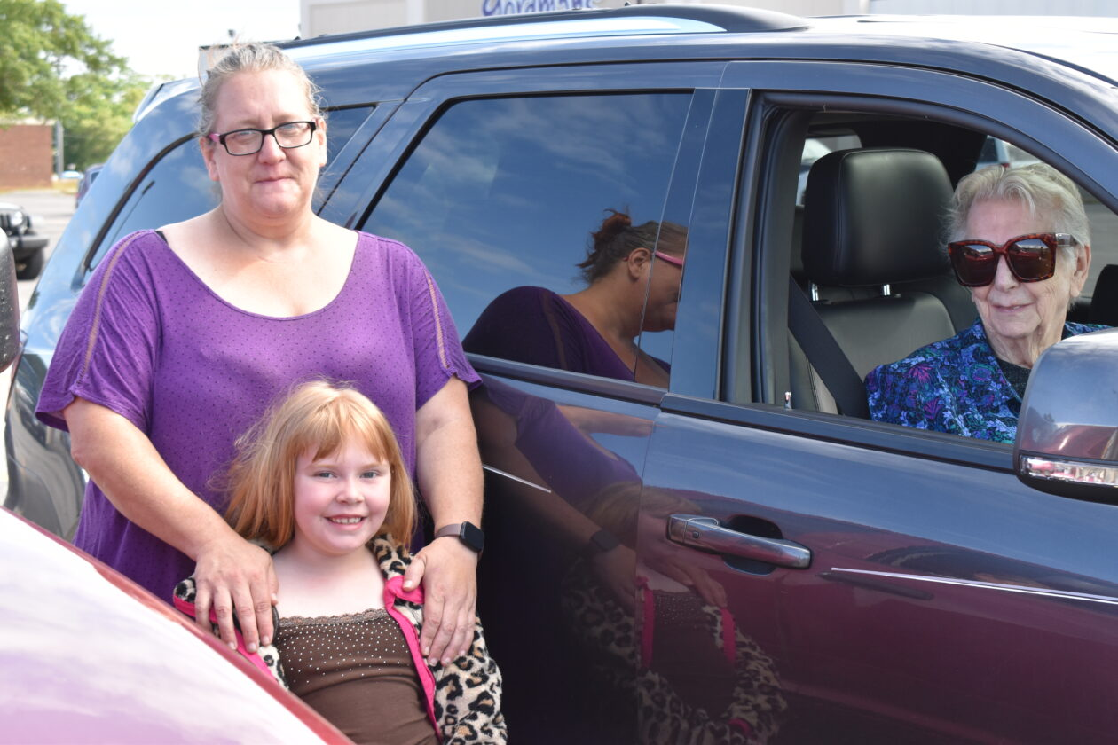 PJ, her daughter and her mother pose inside and outside their car.