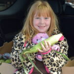 Katrina sits with her family's food in the back of her car holding a stuffed animal and ear of corn.