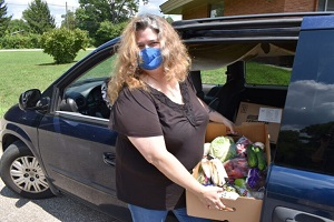 A woman loads a box filled with produce into her car