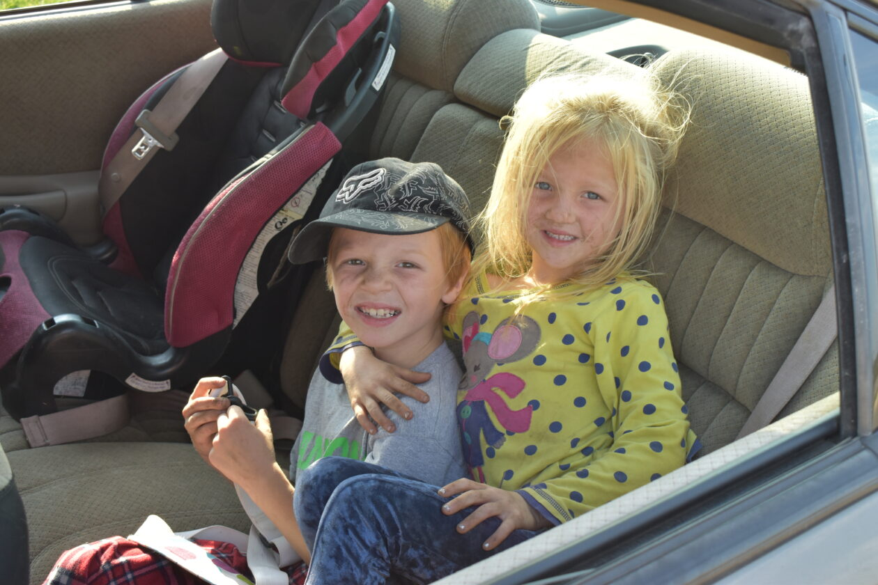 Caydon and Zaeleigh sit in the car while waiting for the Mobile Pantry