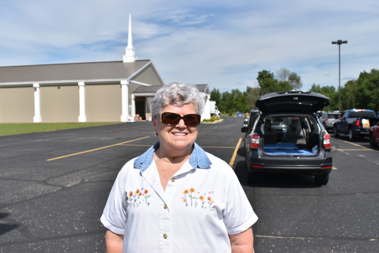 Ruth Anne stands in front of a line of cars leading to the church