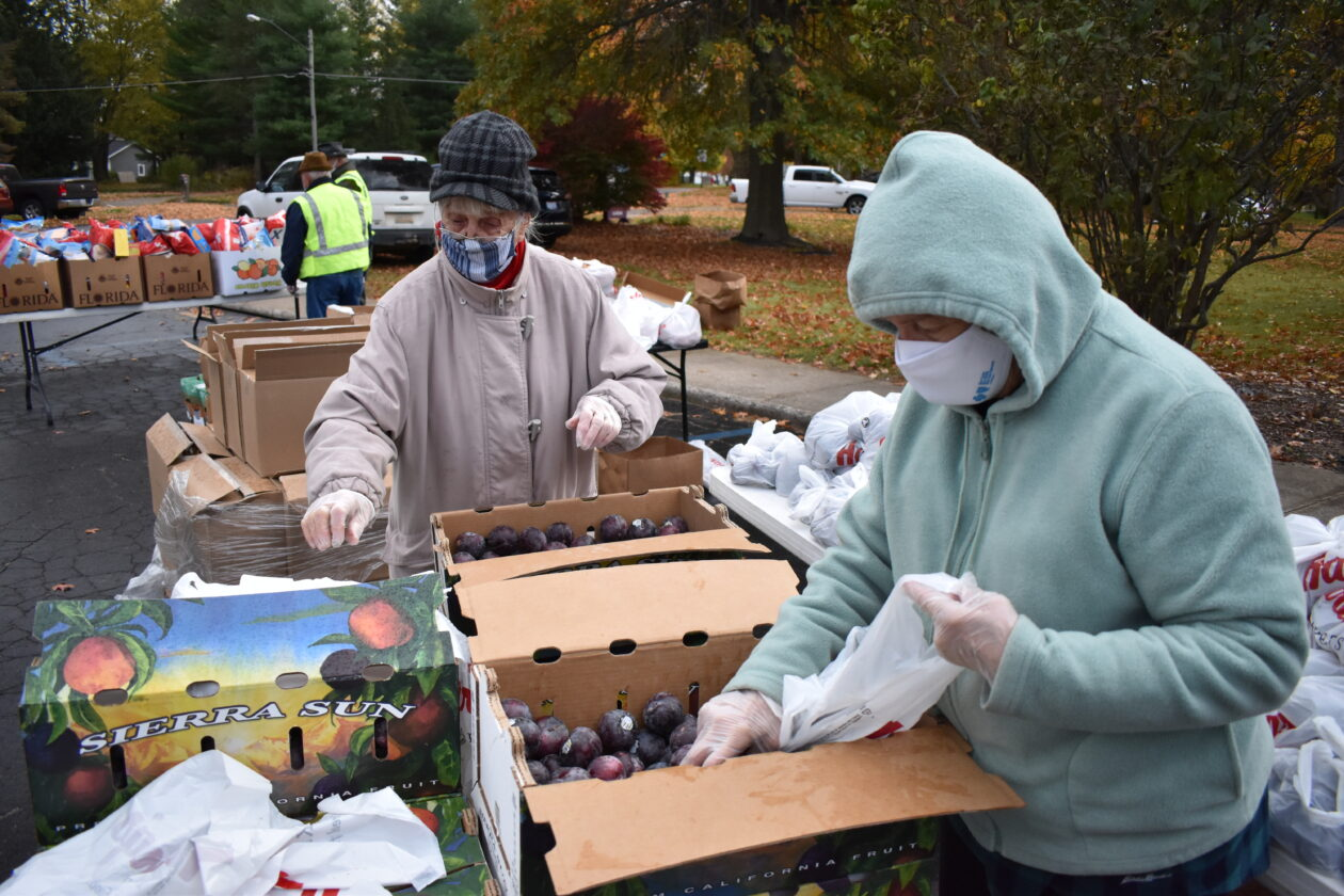 Volunteers bag plums at the Mobile Pantry