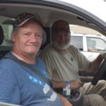 Two men sit in a car waiting for a mobile pantry