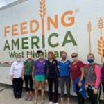 Volunteers stand in front of a food bank truck