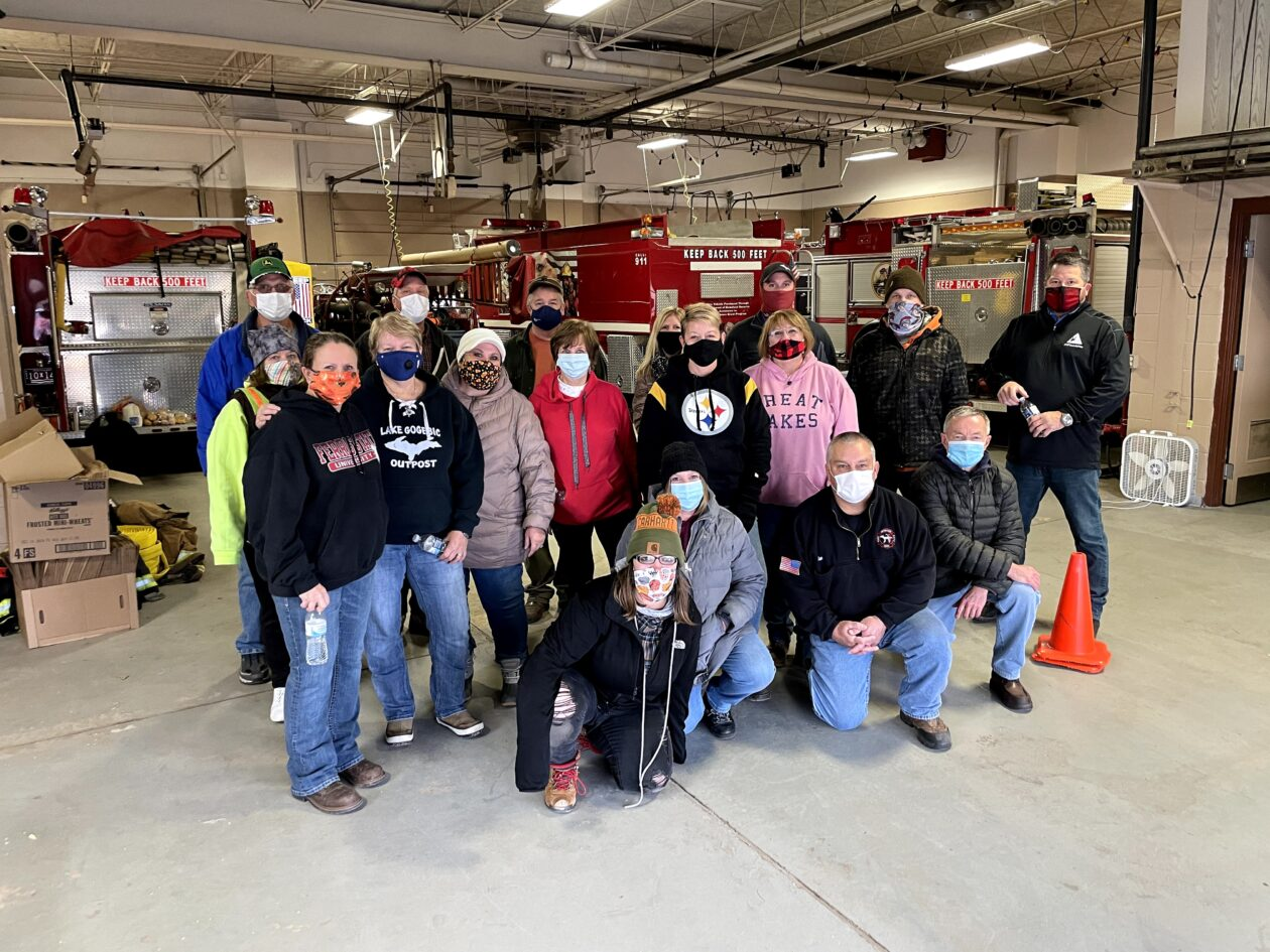 A group of volunteers stand at the firehouse