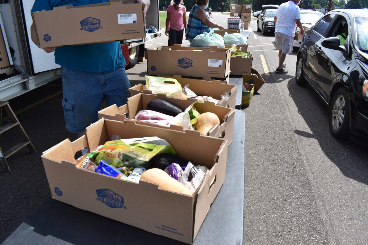 A few boxes of food are lined up waiting to be distributed
