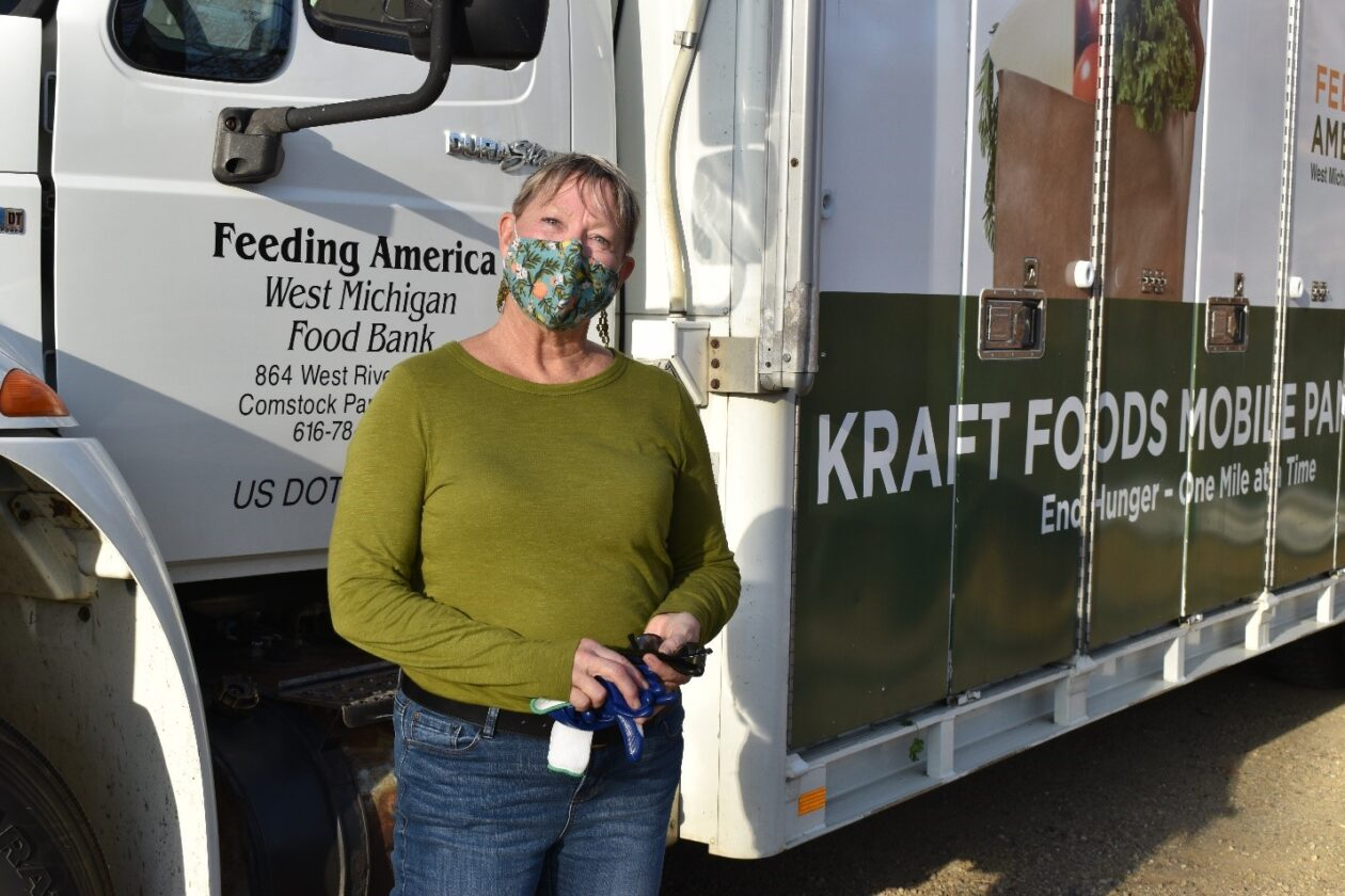 Jeanne stands in front of a Mobile Pantry truck wearing a mask with flowers on it