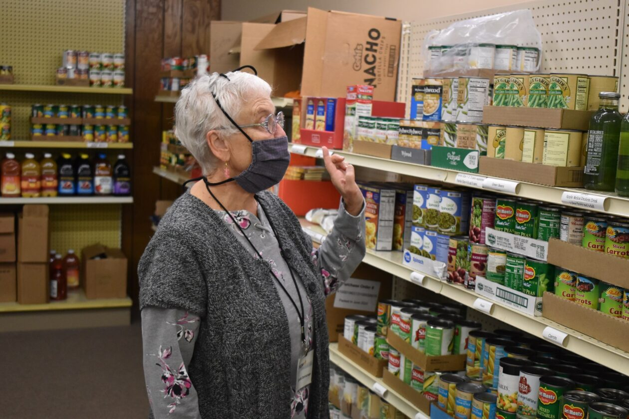 Carole stands in front of shelves of food at the pantry