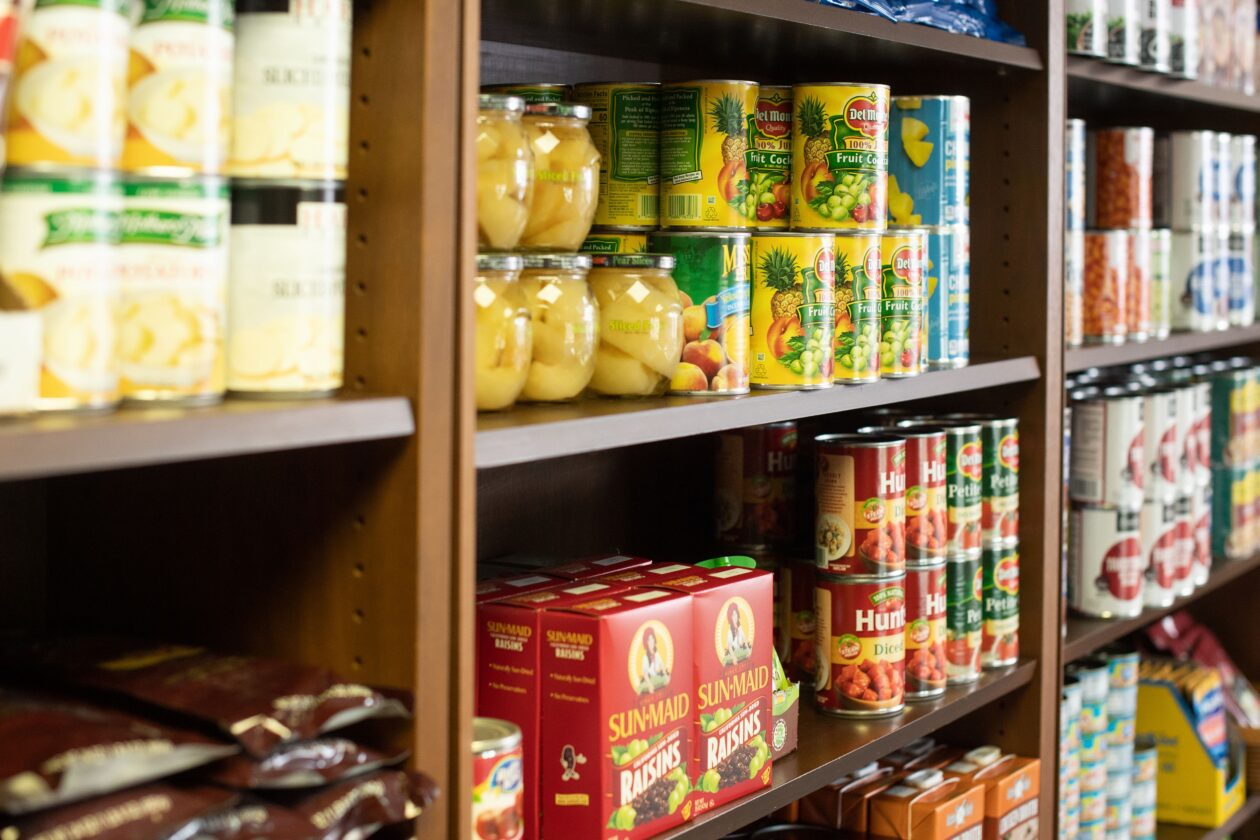 A shelf is stocked with various canned fruits.