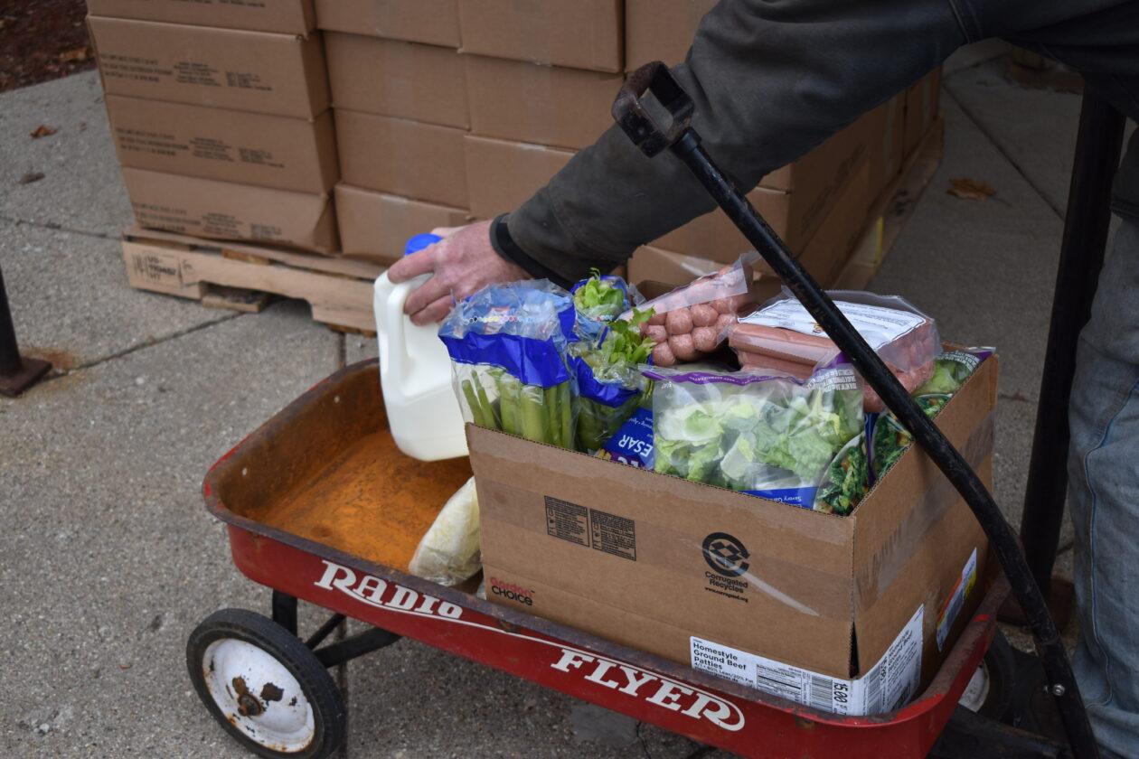 A neighbor loads a wagon with an assortment of food