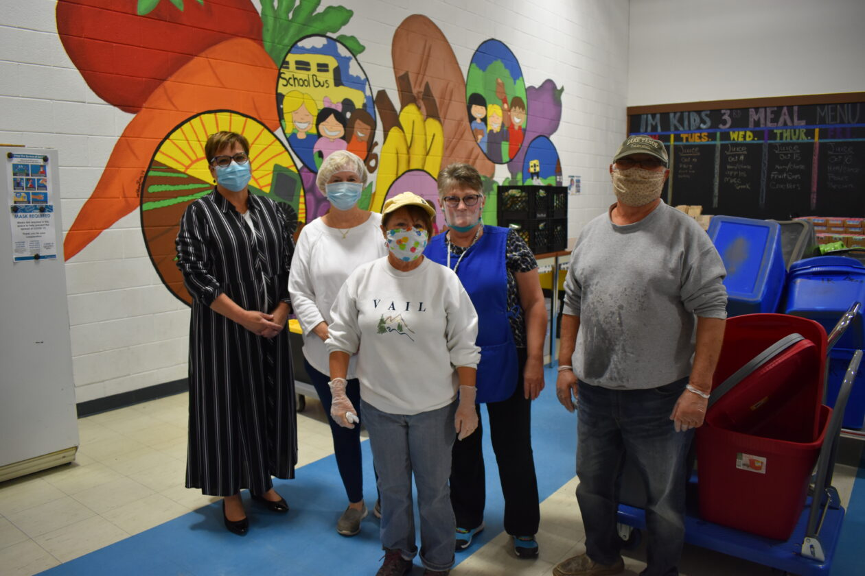 A few volunteers stand in front of a mural of fruit, bread and more at IM Kids' Warehouse